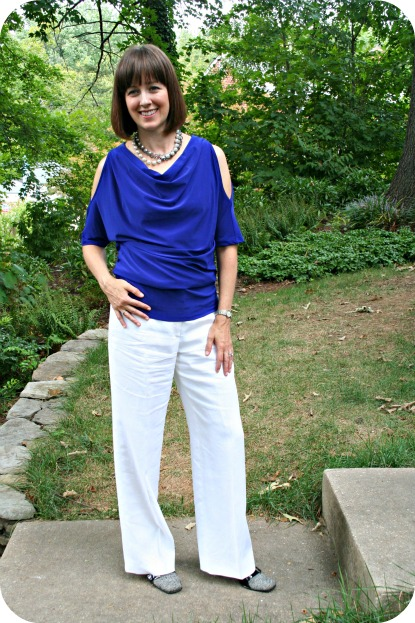 Client Meeting working mom outfit with blue cutout sleeve blouse, white linen trousers, black patterned booties